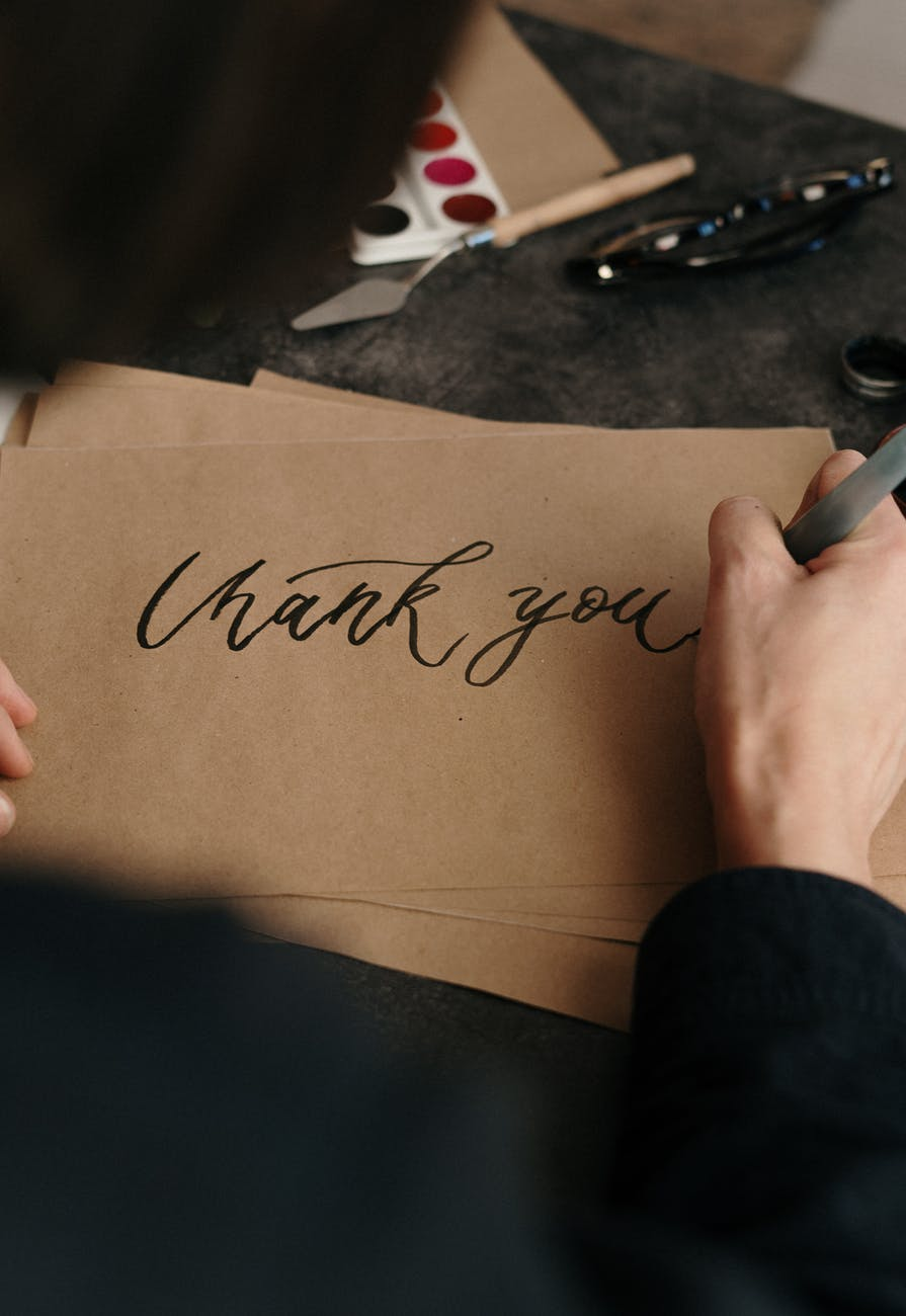 person writing on brown printer paper